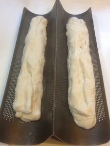 Bread dough rising in a perforated French bread pan
